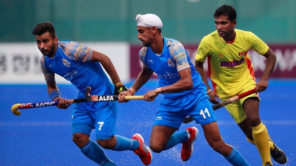 India's Manpreet Singh, left, and Mandeep Singh, center, and Sri Lanka's Mud IKJ Doranegala run for the ball during the Asian Games hockey men's match.