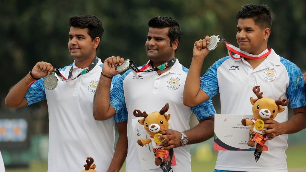 Rajat Chauhan (centre) stands on the podium after his silver medal finish at the Asian Games.