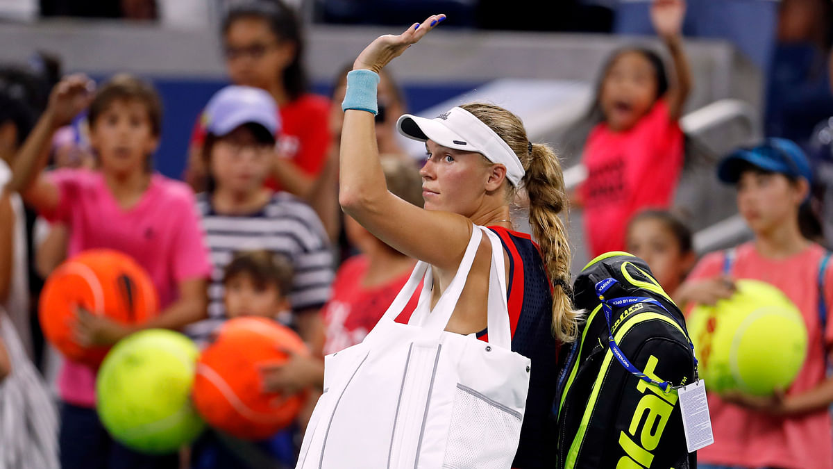 Caroline Wozniacki, of Denmark, waves as she leaves the court after losing to Lesla Tsurenko, of Ukraine, during the second round of the U.S. Open tennis tournament, Thursday