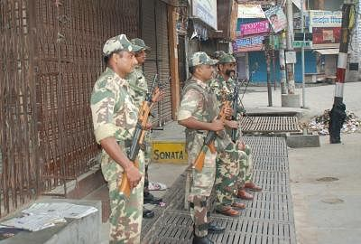 Security personnel stand guard at Muzaffarnagar as Army petrol the streets to defuse tension on Sept 9, 2013. (Photo: IANS)
