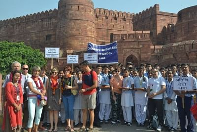 Agra: School students greet tourists at Agra Fort on World Tourism Day, on Sept 27, 2018. (Photo: IANS)