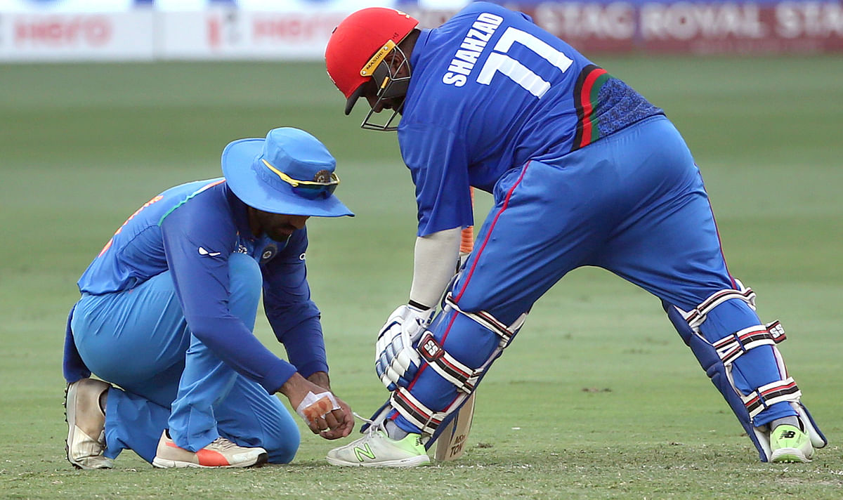 India's Dinesh Karthik, left, ties shoelaces of Afghanistan's Mohammad Shahzad during the one day international cricket match of Asia Cup between India and Afghanistan.