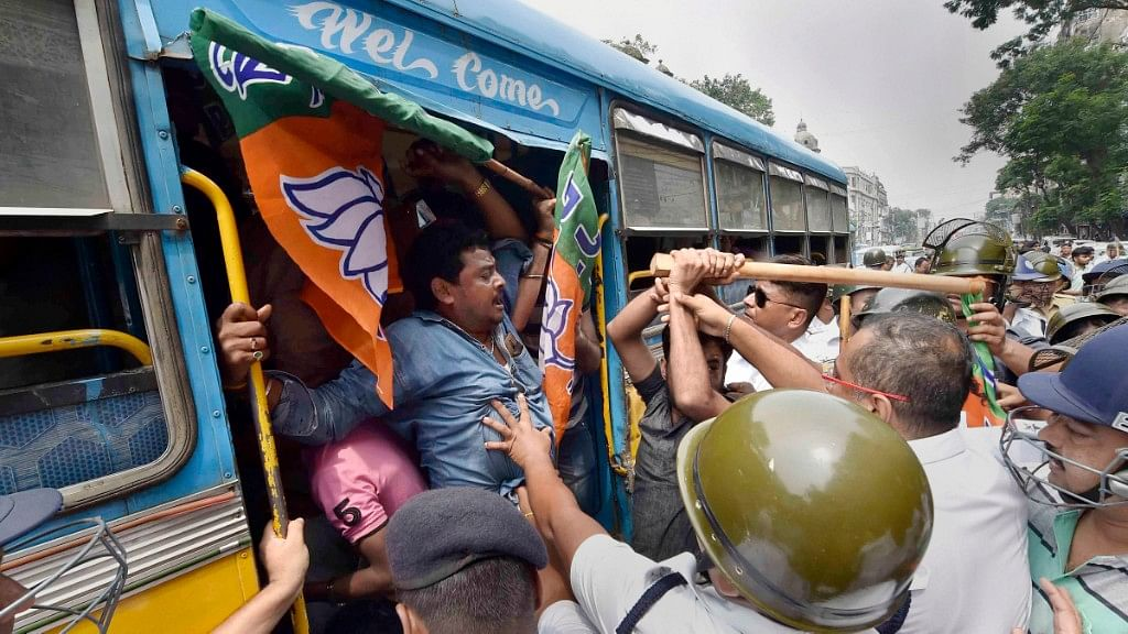 Police personnel detain BJP activists protesting during Bangla Bandh strike against the State Government.