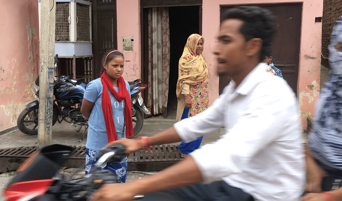 Raeesa Begum (head covered) outside her home in Rajapur village on the outskirts of Ghaziabad.