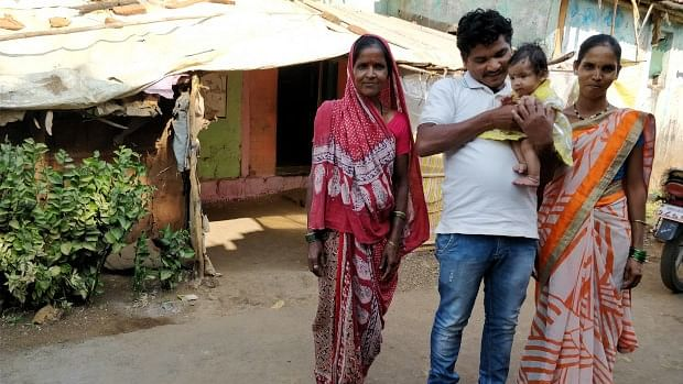 Kailash Burange holds his one-year-old daughter Sanskruti, as wife Arti and his mother stand next to him.