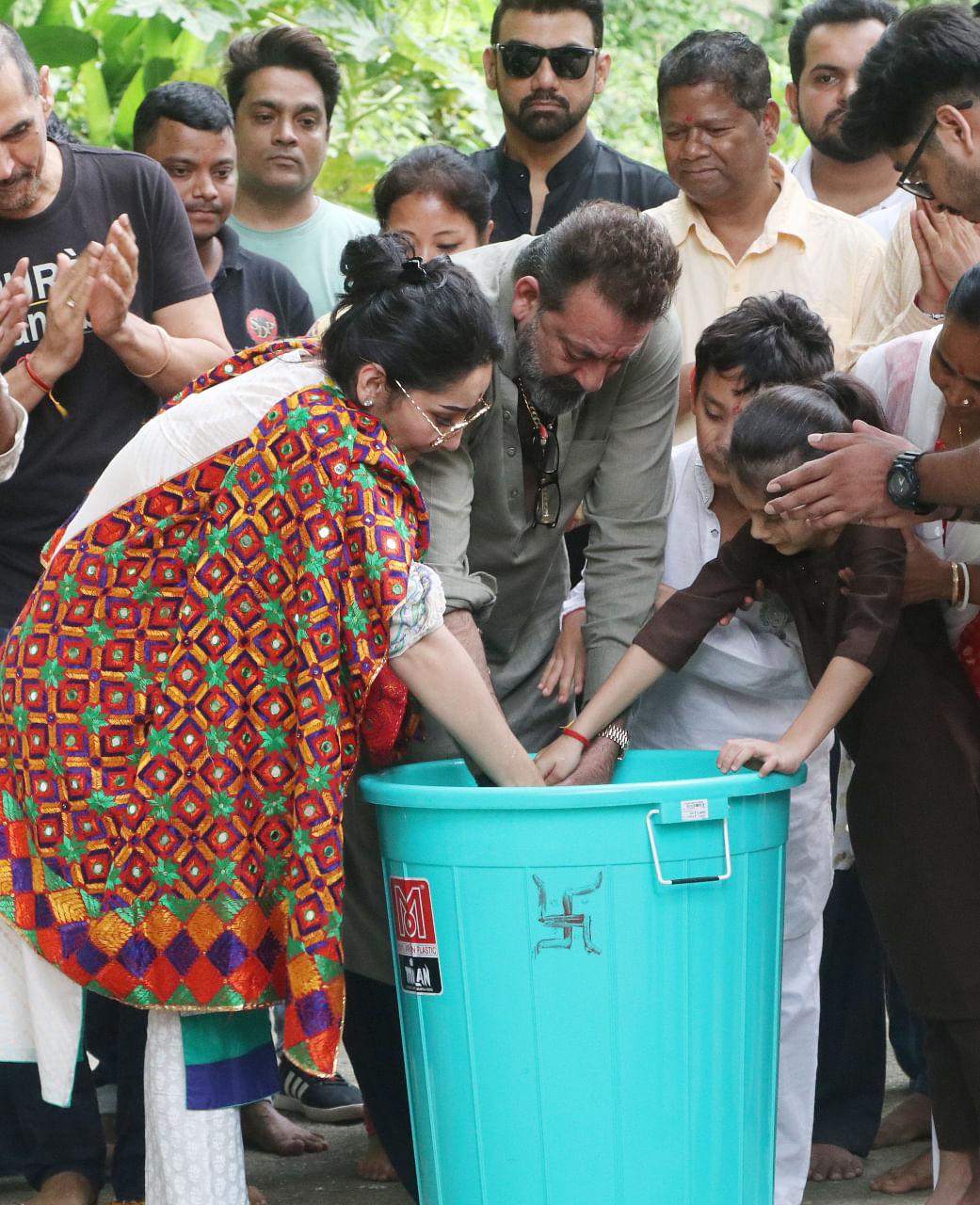 Sanjay, Maanyata and their kids immerse Ganesh idol in a bucket.