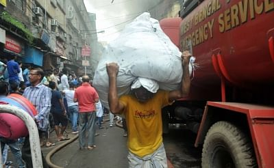 Kolkata: A man carries a sack to safe place from Bagri Market where a massive fire broke out around 2.45 a.m. in Kolkata on Sept 16, 2018. (Photo: Kuntal Chakrabarty/IANS)