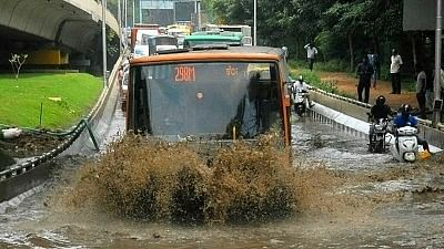 Bengaluru: Commuters struggle through a water-logged street after heavy rains lashed Bengaluru, on 25 September, 2018.