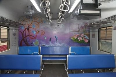 Mumbai: An artist busy painting the interiors of a ladies coach of a suburban train, in Mumbai on Sept 26, 2018. In an effort to provide a pleasing ride to women commuters, the Western Railway has painted the interiors of two ladies coaches of suburban trains with eye-catching scenic views, an official spokesperson said here on Wednesday. The painting shows birds singing on trees, dolphins jumping out of the water, a tiny land mass with coconut trees, lush greenery and flowery bushes. (Photo: IA