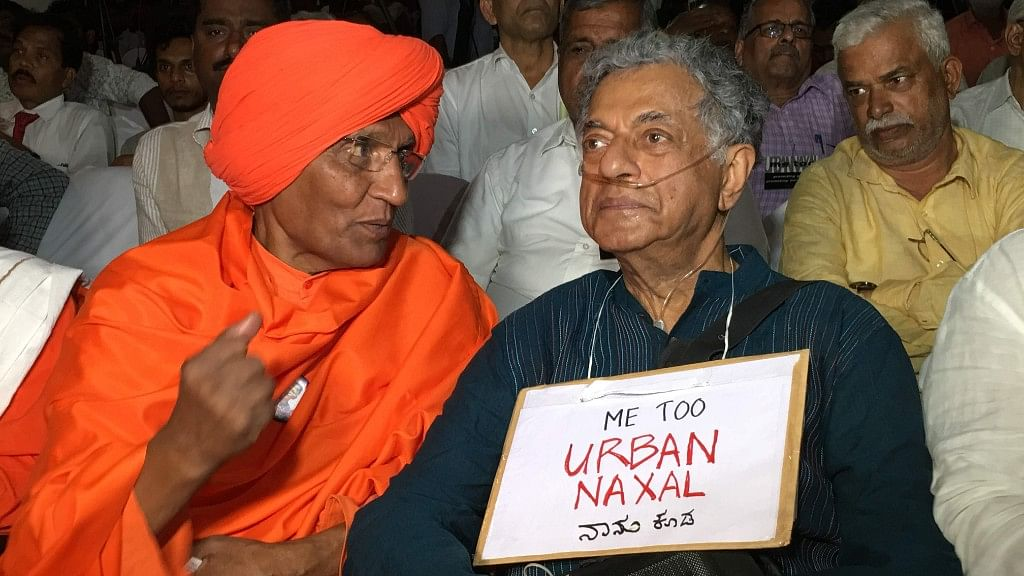 "Playwright Girish Karnad wearing a ""MeTooUrbanNaxal"" placard at a function commemorating Garui Lankesh's first death anniversary."