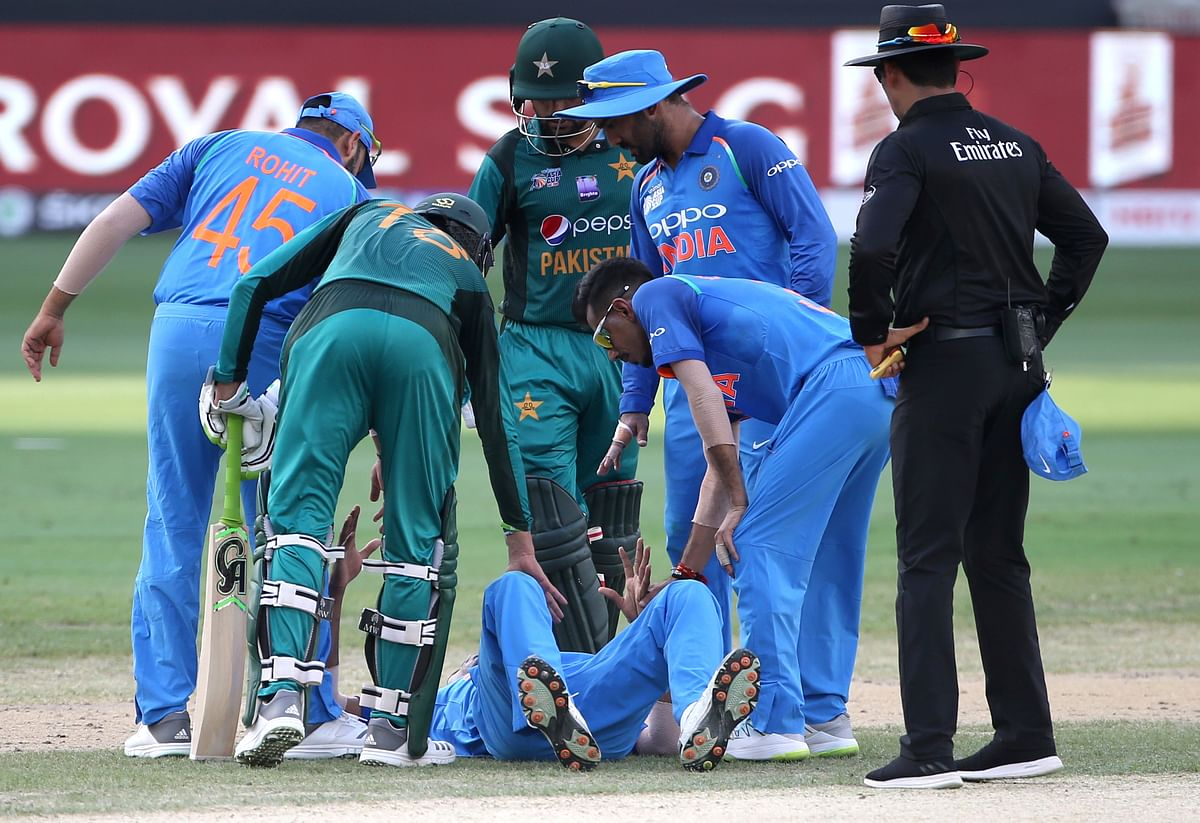 Indian and Pakistani players check on India's Hardik Pandya, on ground, after he fell during the one day international cricket match of Asia Cup between India and Pakistan in Dubai, United Arab Emirates, Wednesday, Sept. 19, 2018.