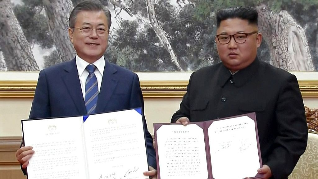 South Korean President Moon Jae-in, left, and North Korean leader Kim Jong Un pose after signing documents in Pyongyang, North Korea on 19 September, 2019.