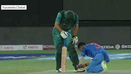 Yuzvendra Chahal tying Pakistani pacer Usman Khan's shoelaces.