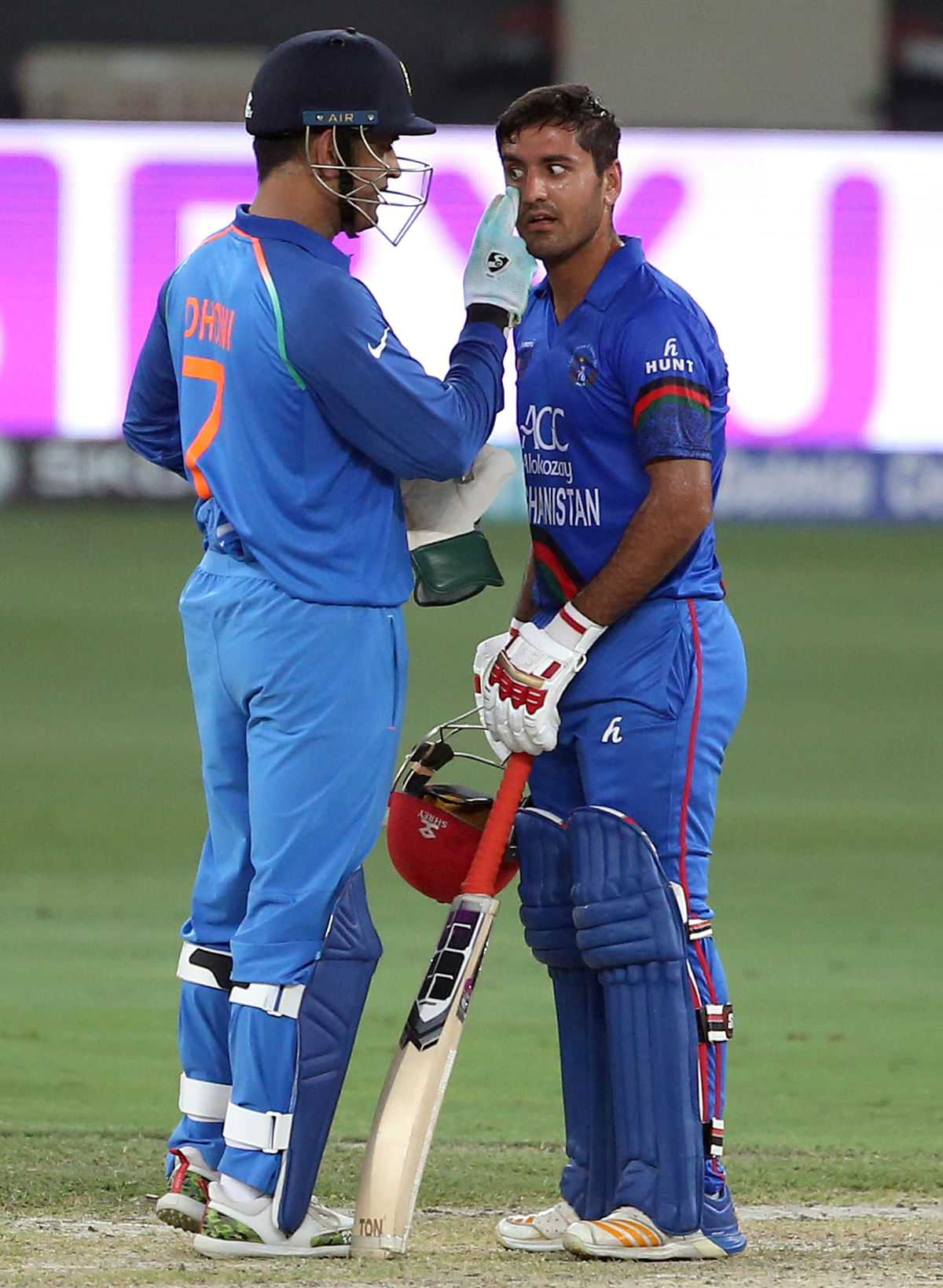 India's Mahendra Singh Dhoni, left, checks the eye of Afghanistan's Najibullah Zadran during the one day international cricket match of Asia Cup between India and Afghanistan in Dubai.