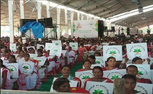 In the MohFW photo, the women can be seen holding placards which have the logo and the name of the scheme on it.