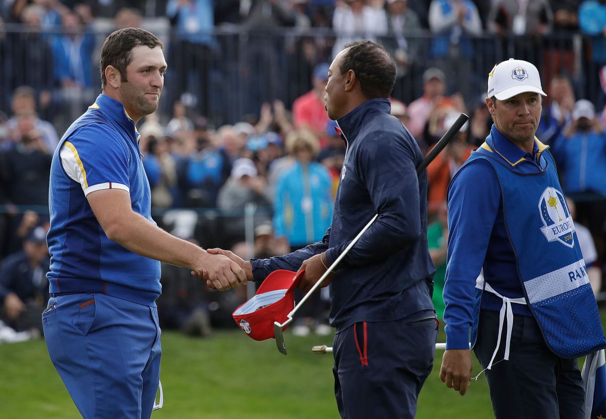 Europe's Jon Rahm, left, shakes hands with Tiger Woods of the US after beating them in a singles match on the final day of the 42nd Ryder Cup.