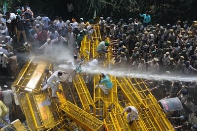 New Delhi: Police charge water cannons to disperse protesting farmers at the Uttar Pradesh-Delhi border in Ghaziabad on Oct 2, 2018. The protest by thousands of farmers who were marching to Delhi from Haridwar under the banner of Kisan Kranti Yatra demanding complete loan waiver and reduction in electricity tariff among other turned violent after they were stopped from entering the national capital. (Photo: IANS)
