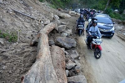PALU, Oct. 1, 2018 (Xinhua) -- People drive past debris of landslide after the earthquake in Palu, Central Sulawesi, Indonesia, Oct. 1, 2018. Over 1,203 people were killed in Palu, Donggala district, Parigi Mountong district and North Mamuju district, according to the Disaster Management Institute of Indonesia, Care for Humanity and the Humanity Data Center. (Xinhua/Agung Kuncahya B./IANS)