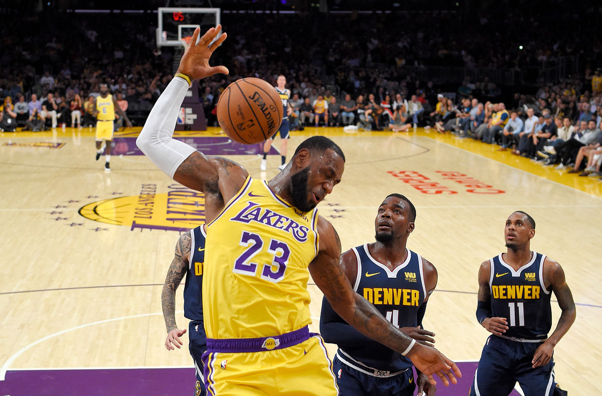 Los Angeles Lakers forward LeBron James, left, dunks as Denver Nuggets forward Paul Millsap, center, and guard Monte Morris watch during the first half of an NBA basketball game in Los Angeles.