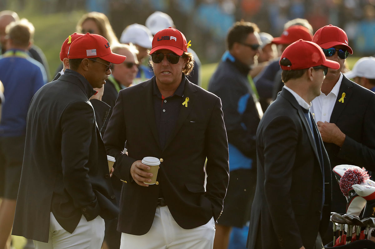 Tiger Woods of the US, left, and Phil Mickelson of the US wait for the closing ceremony after Europe won the Ryder Cup.