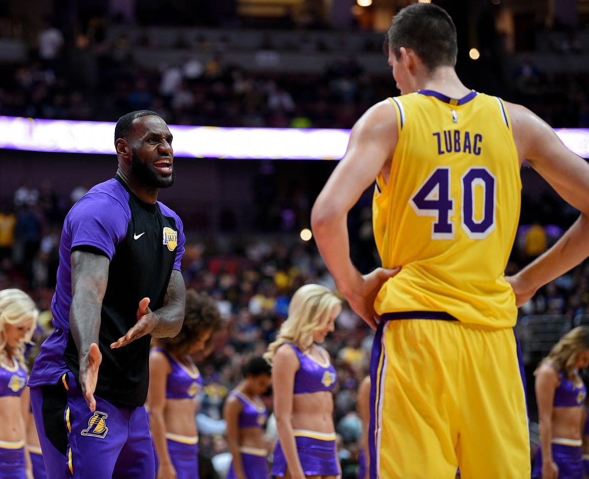 Los Angeles Lakers forward LeBron James, left, speaks with center Ivica Zubac during a timeout in the first half of an NBA preseason basketball game against the Los Angeles Clippers.