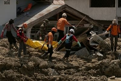 PALU, Oct. 10, 2018 (Xinhua) -- Rescuers carry the body of a victim in Palu, Central Sulawesi, Indonesia, on Oct. 10, 2018. The Indonesian national disaster agency put the death toll from multiple strong quakes and an ensuing tsunami in Central Sulawesi province at 2,045 on Wednesday, a day before the search operation ended. (Xinhua/Wang Shen/IANS)