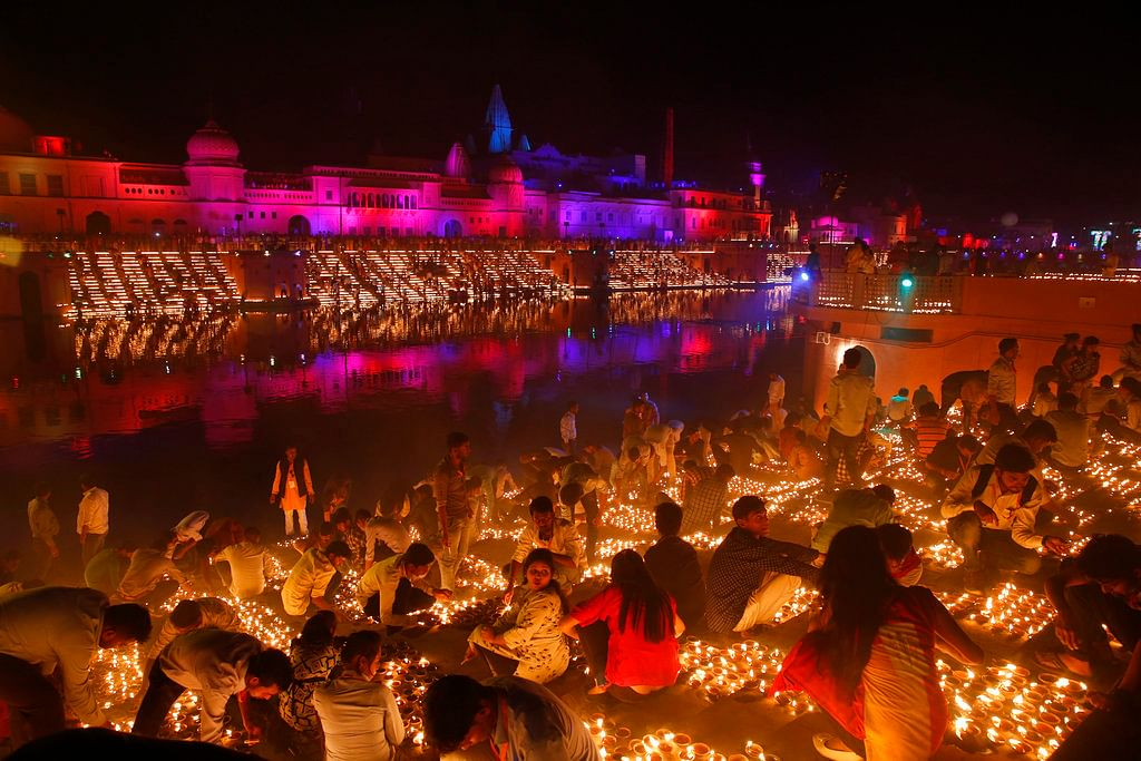 Devotees light earthen lamps on the banks of the River Sarayu as part of Diwali celebrations in Ayodhya.