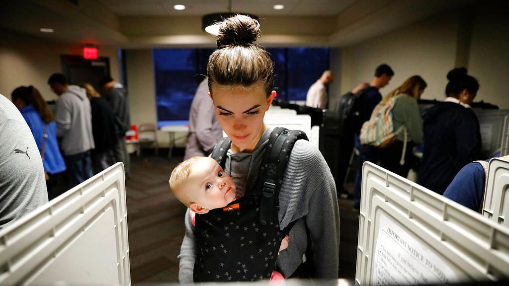 Kristen Leach votes with her six-month-old daughter, Nora, on election day in Atlanta, Tuesday, 6 November.