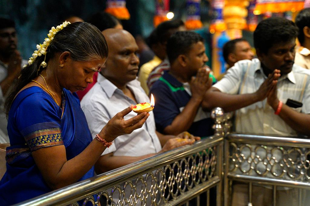 Hindu devotees praying at a temple during the Deepavali celebration in the Batu Caves of Selangor, Malaysia.