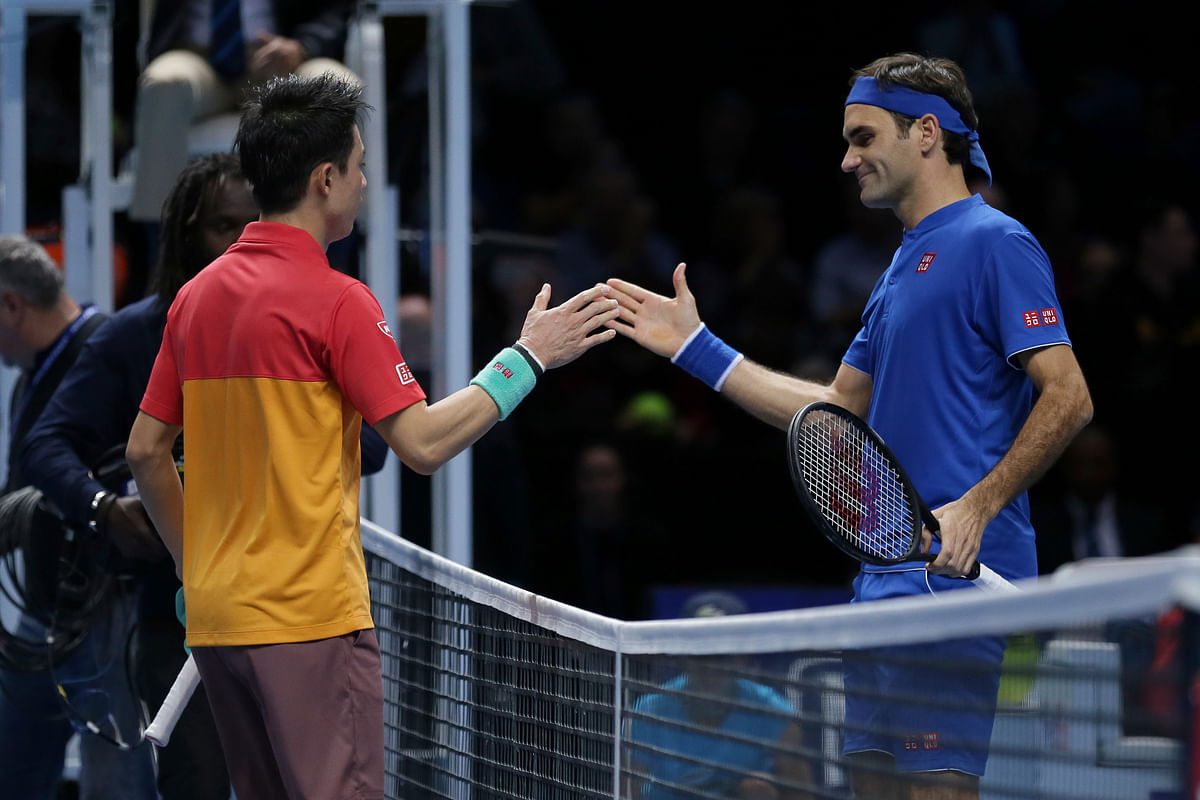 Nishikori and Federer shake hands at the end of their Group Hewitt clash in London