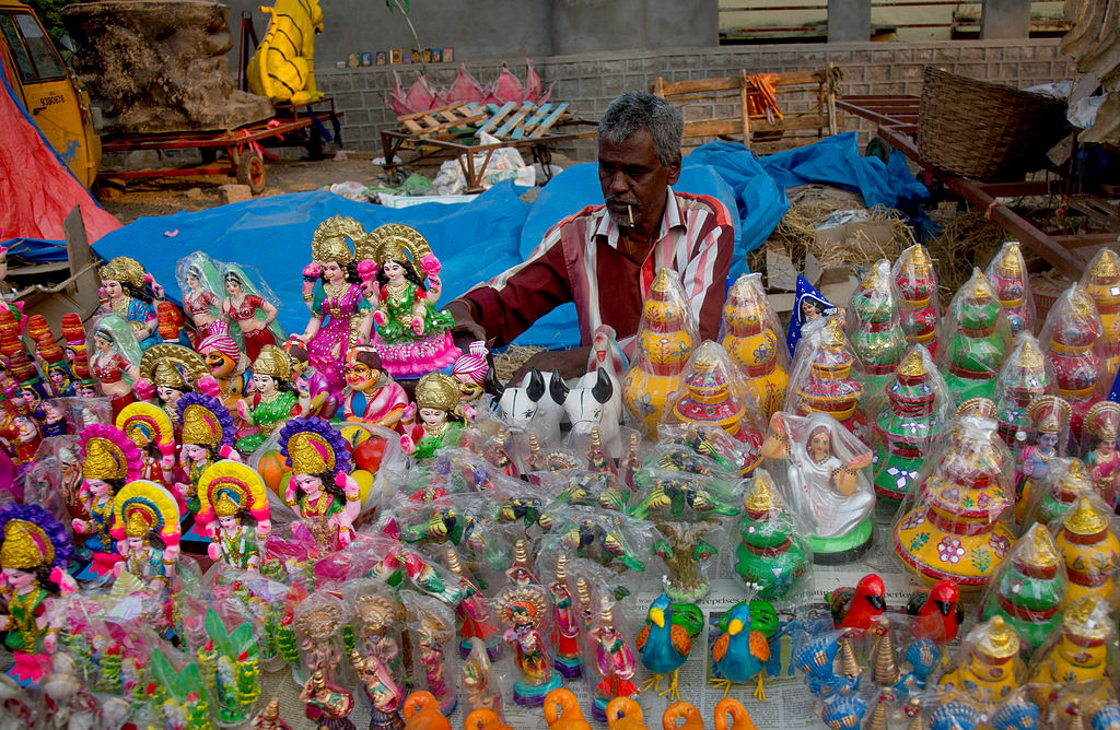 A vendor arranges idols of Hindu goddess Lakshmi and other decorative articles at a road side market ahead of Diwali, the festival of lights in Hyderabad.