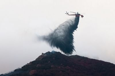 THOUSAND OAKS , Nov. 14, 2018 (Xinhua) -- A helicopter drops water on wildfires in Thousand Oaks, California of the United States, on Nov. 13, 2018. The fire in Southern California continued to destroy homes. (Xinhua/Qian Weizhong/IANS)