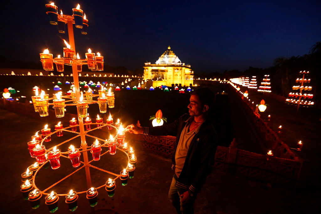 An Indian man light lamps at the Akshardham temple on the eve of Diwali, the festival of lights in Gandhinagar.