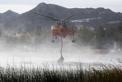THOUSAND OAKS , Nov. 14, 2018 (Xinhua) -- A helicopter sucks water from a lake in Thousand Oaks, California of the United States, on Nov. 13, 2018. The fire in Southern California continued to destroy homes. (Xinhua/Qian Weizhong/IANS)