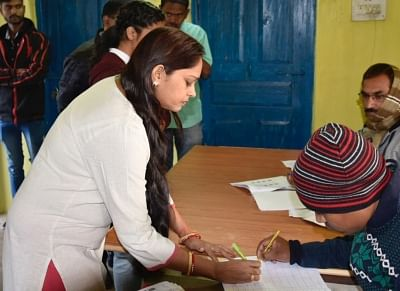 Narayanpur: A woman signs a register before casting her vote during the 1st phase of Chhattisgarh Assembly Elections at a polling booth in Narayanpur on Nov 12, 2018. (Photo: IANS/PIB)
