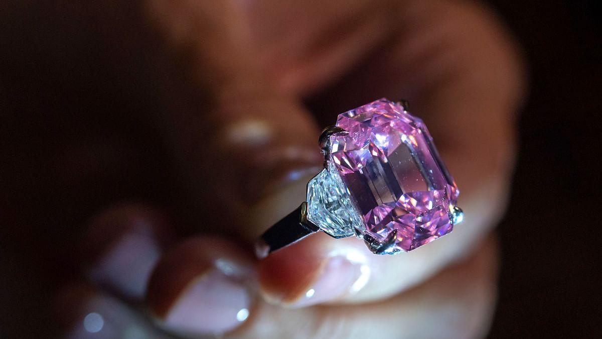 An auctioneer displays an 18.96-carat fancy vivid pink diamond.