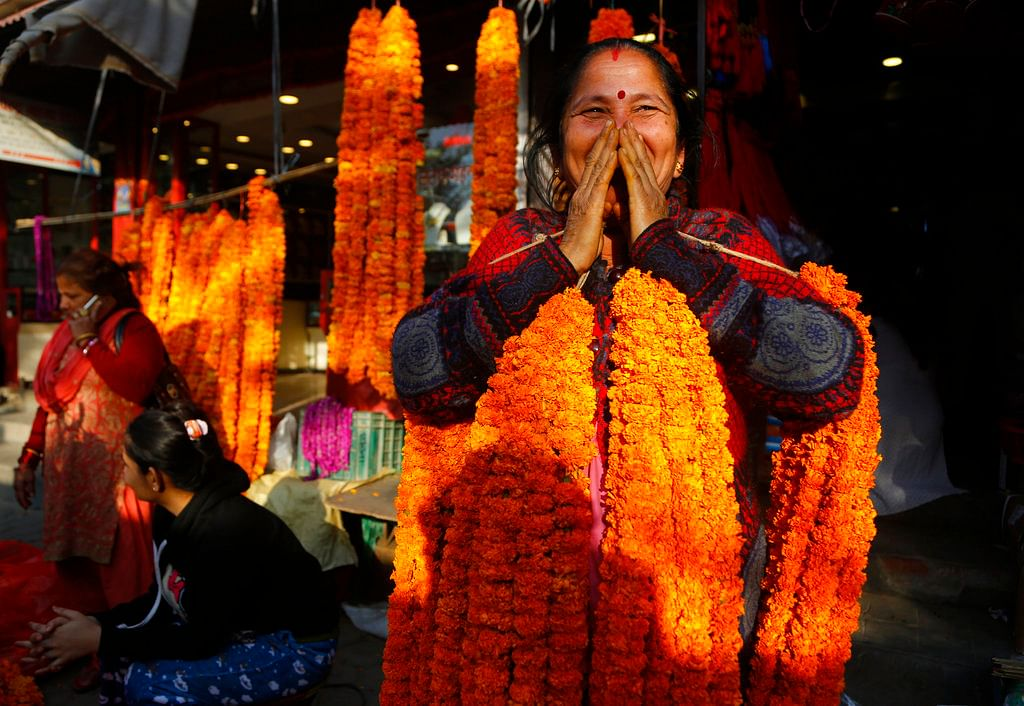 A Nepalese vendor reacts as she sells marigold flower garlands during Tihar festival in Kathmandu, Nepal.