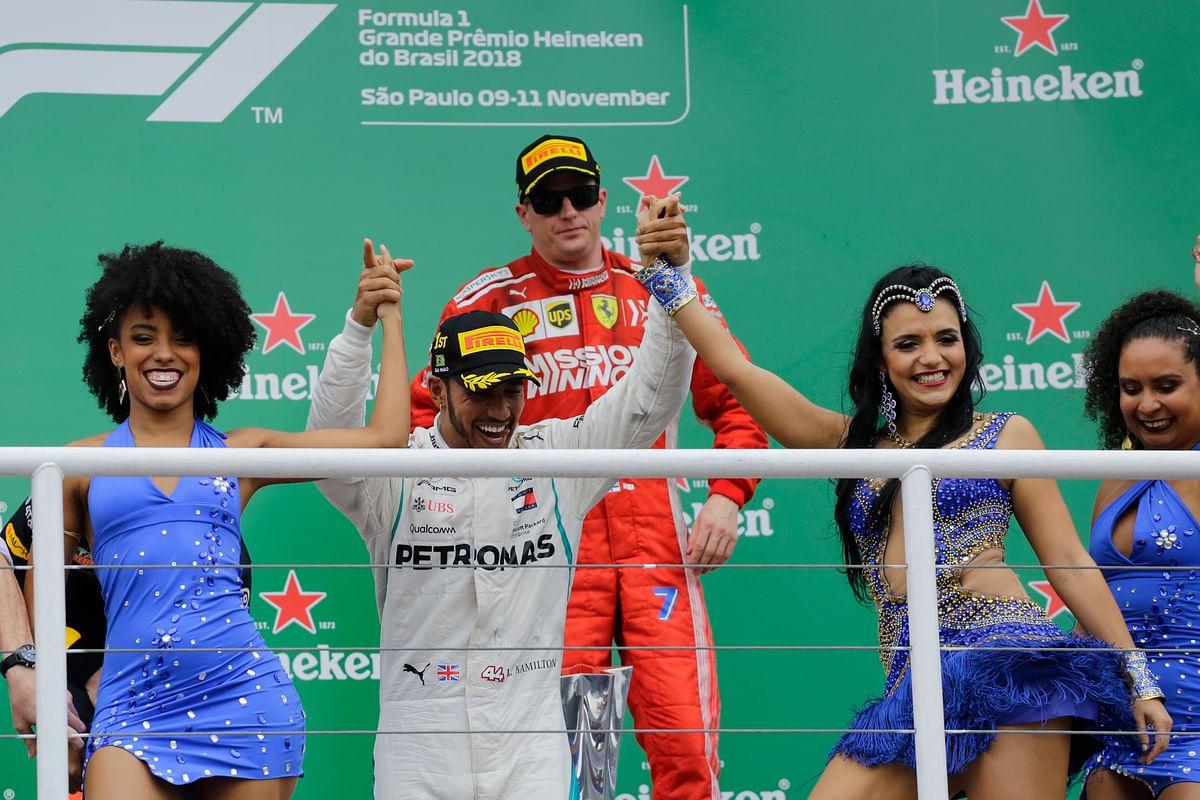 Lewis Hamilton rejoices at the podium in Sao Paulo as Kimi Raikkonen looks on