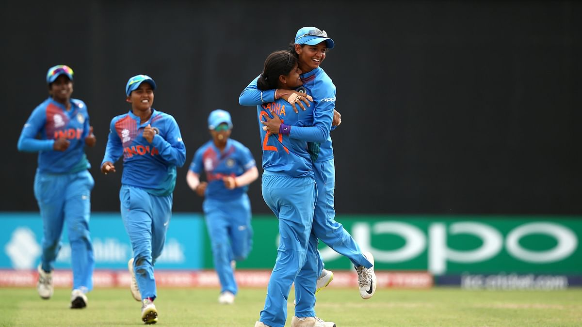 Radha Yadav celebrates a wicket with her teammates.