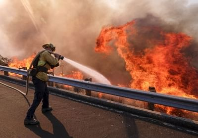 SIMI VALLEY, Nov. 13, 2018 (Xinhua) --  A firefighter battles wildfire near a freeway in Simi Valley, California, the United States on Nov. 12, 2018. The fire in Southern California continued to destroy homes.  (Xinhua/Zhao Hanrong/IANS)