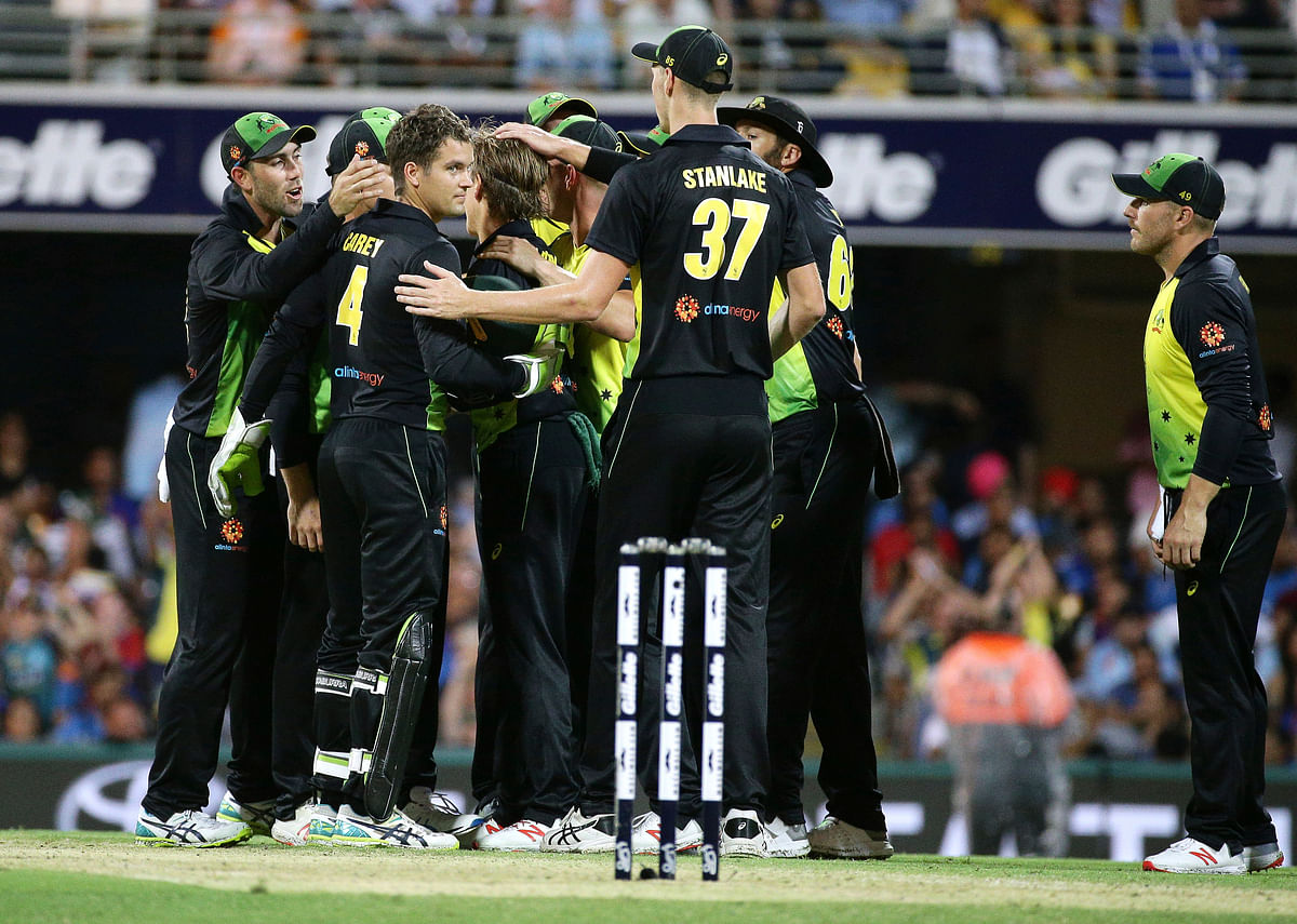 Australian players congratulate Adam Zampa (center, back-to-camera) after he dismissed KL Rahul