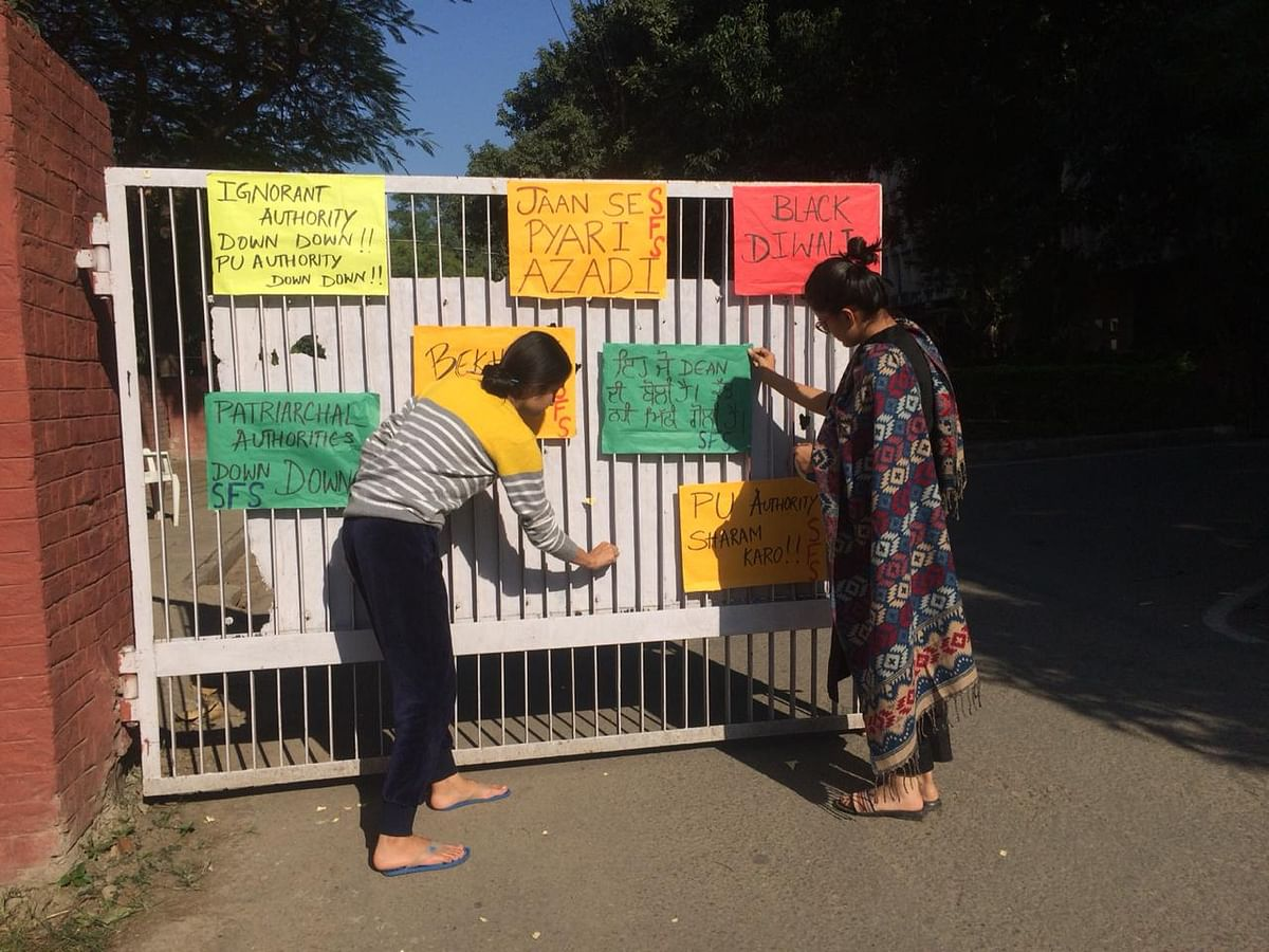 Women put up posters at the Panjab University in Chandigarh.