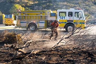 SIMI VALLEY, Nov. 13, 2018 (Xinhua) --  A firefighter cleans the remains of a tree destroyed by fire in Simi Valley, California, the United States on Nov. 12, 2018. The fire in Southern California continued to destroy homes. (Xinhua/Qian Weizhong/IANS)