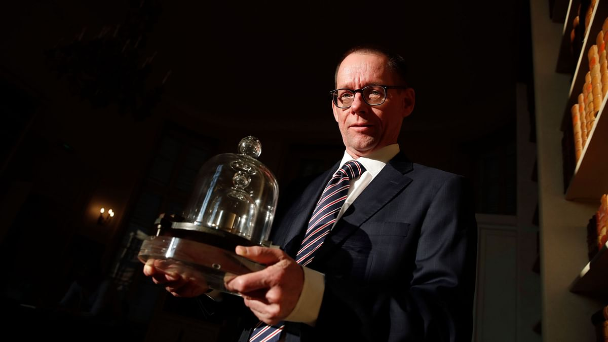 The head of BIPM (International Bureau of Weights and Measures) Martin JT Milton holds a replica of the International Prototype Kilogram in Sevres, near Paris.