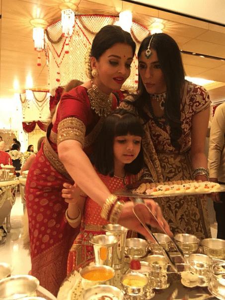 Aishwarya Rai with Aaradhya serving food to guests.