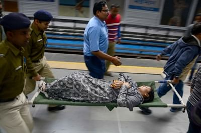 Kolkata: Passengers being taken for treatment after an air-conditioned rake of a metro train in Kolkata caught fire on Dec 27, 2018. Thick smoke was seen coming out of the second compartment of a Dumdum-bound metro rake between Maidan and Rabindra Sadan metro station around 5 p.m. Many passengers, who were evacuated from the train, complained that they were stranded for more than half-an-hour after the fire incident. They claimed some of the passengers fell ill due to the smoke and alleged that