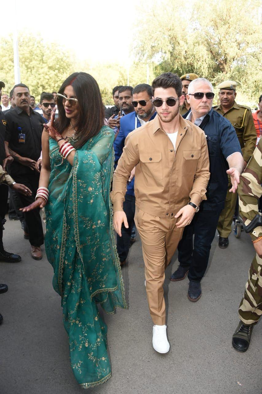 Priyanka and Nick wave at the cameras as they arrive at Jodhpur airport.