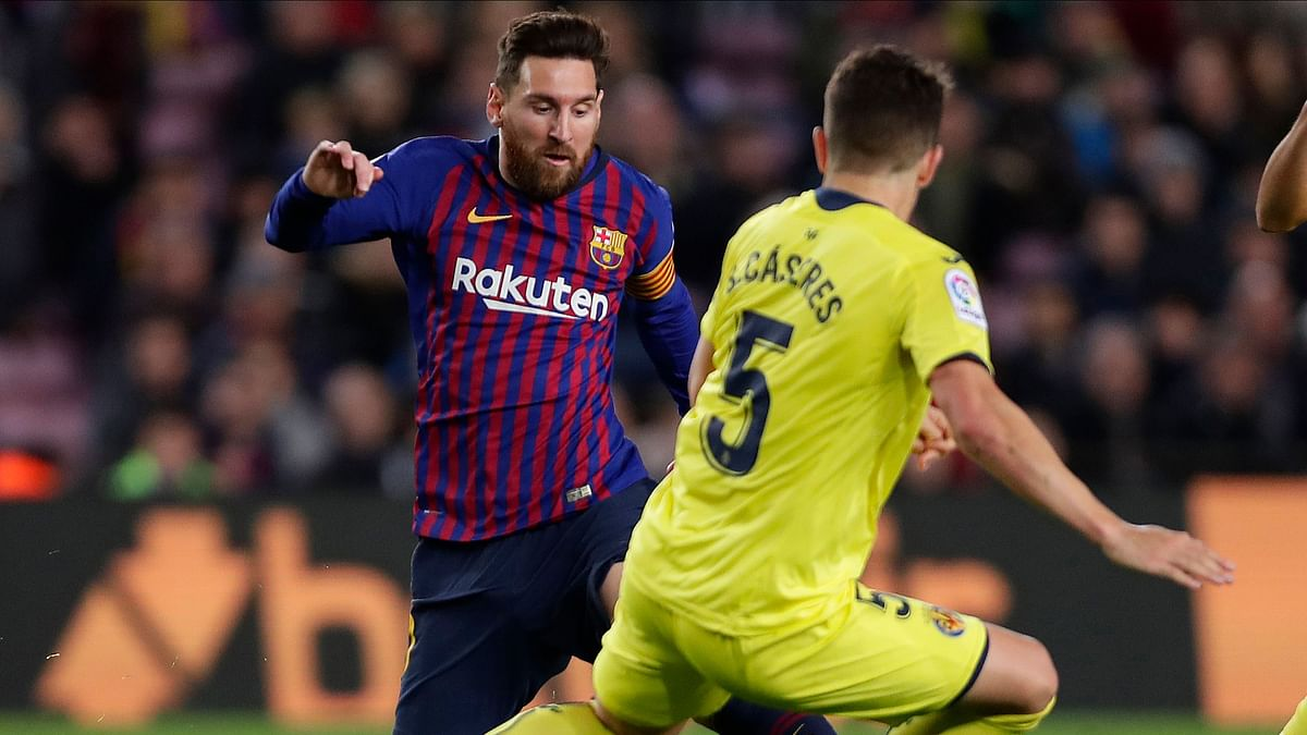 FC Barcelona's Lionel Messi, left, duels for the ball with Villarreal's Santiago Caseres during the Spanish La Liga soccer match between FC Barcelona and Villarreal.