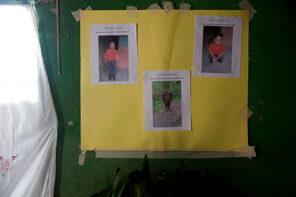 A poster with photo copies that show Felipe Gomez Alonzo is taped to a wall as part of a makeshift altar honoring the 8-year-old, inside his mother's home in Yalambojoch, Guatemala on 29 December 2018.
