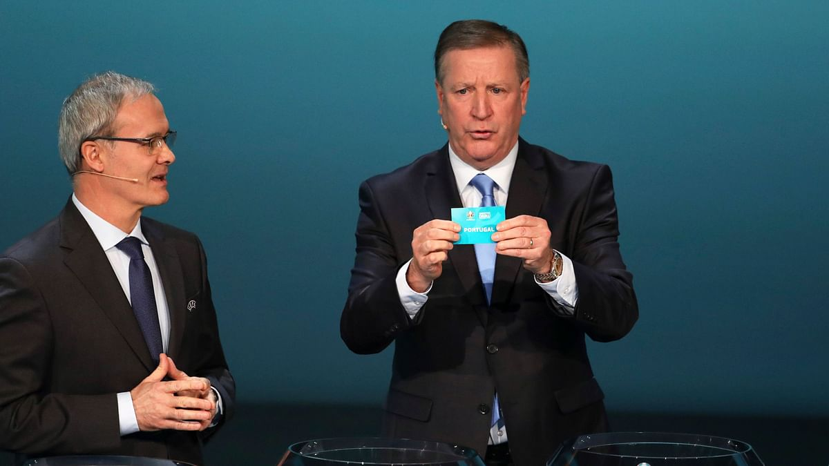 UEFA Deputy General Secretary Giorgio Marchetti (left) gestures as former Irish footballer Ronnie Whelan draws Portugal during the UEFA Euro 2020 qualifying draw at the Convention Centre in Dublin in Ireland on Sunday, December 2, 2018.